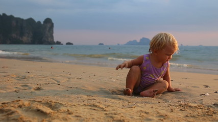 blonde baby girl in purple swimsuit play with seashell near sand
