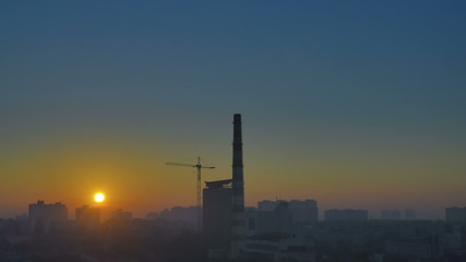 The sunrise by the foggy industrial landscape
