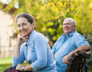 couple sitting on   bench in autumn park.
