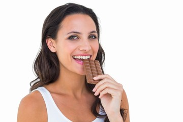 Pretty brunette eating bar of chocolate
