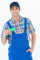 Confident plumber showing green card