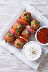 meatballs on skewers and sauces vertical top view