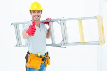 Worker carrying step ladder while showing thumbs up