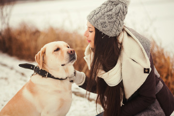 Young girl with love looking at your dog. Winter portrait.