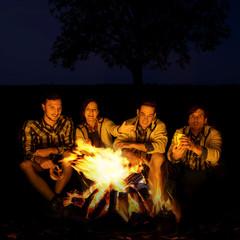 Junge Menschen am nächtlichen Lagerfeuer