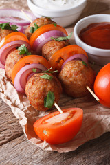 meatballs on skewers with onions and tomatoes. Vertical