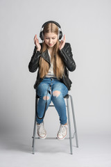 Girl in wired headphones is sitting and listening music