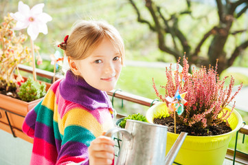 Adorable little girl watering plants on the balcony