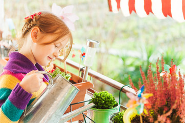 Adorable little girl watering plants on the balcony