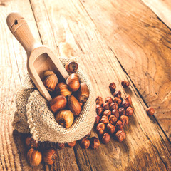 Hazelnuts in a rural bag on a wooden table and a spoon for scoop