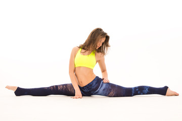 young woman in yellow shirt sits on splits