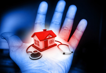 House and stethoscope in human hand .