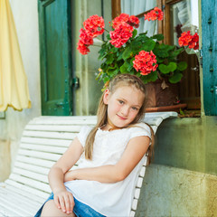 Adorable little girl resting on a bench on a nice warm day