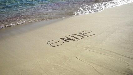 Wort Ende im Sand wird von Wellen weggespült