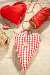 Two homemade sewed red cotton love hearts. Closeup.