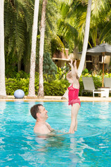 Active father teaching his toddler daughter to swim in pool