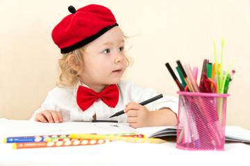 Cute child girl drawing with colorful pencils in preschool