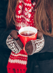 female hands in mittens holding a cup of tea