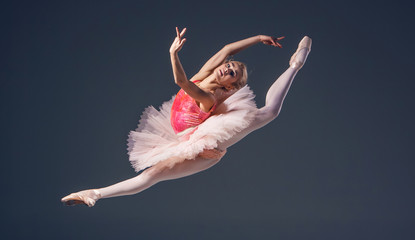 Beautiful female ballet dancer on a grey background. Ballerina