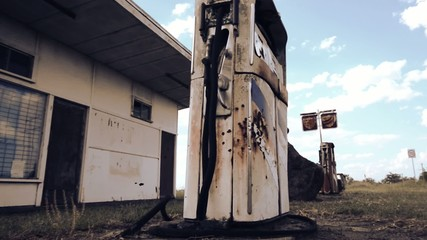 Rusted on pump put the front of an abandoned fuel station.