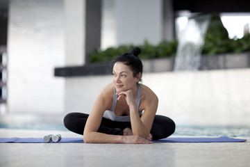 A woman sitting on her fitness mat
