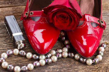 pair of red shoes with rose flower and pearl jewellery on wood