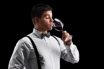 Elegant young guy drinking wine
