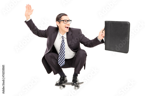 Excited businessman riding a skateboard to work