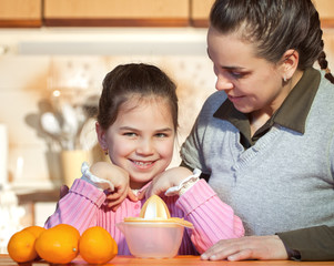 Woman and daughter making fresh fruit juice
