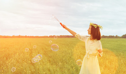 Beautiful woman blowing soap bubbles in summer