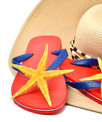 red flip flops with starfishes, sunglasses  and a seashell isola