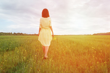Woman walking on summer meadow at sunny day