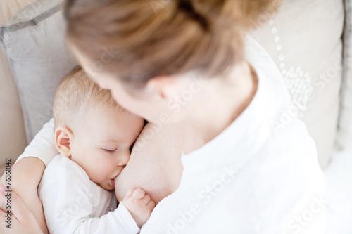 Leinwanddruck Bild Young mother breastfeeding the newborm baby - indoors