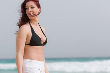 Junge rothaarige Frau am Strand