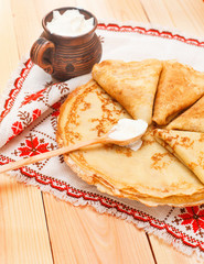 Pancakes with cream on wooden table