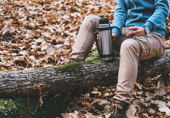 Hiker woman holding a cup of tea and thermos in autumn forest