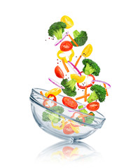 vegetables falling into a glass bowl on a white background. Conc
