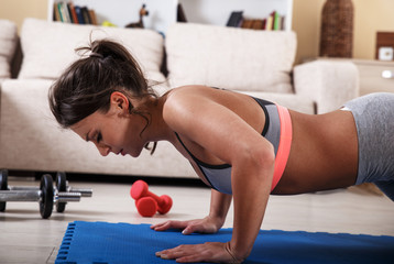Attractive female exercise at home.Fitness.Doing push ups.
