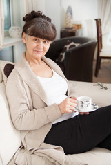 Pension age good looking woman with cup of tea