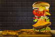 Cheeseburger with flying ingredients, copy space