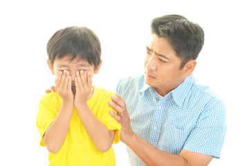 泣いている男の子と心配する親