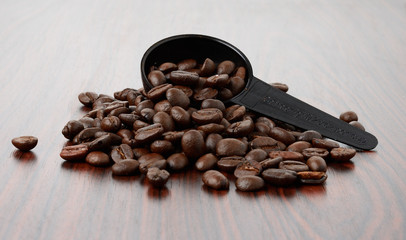 Spoon of coffee bean on wood texture isolated on white backgroun