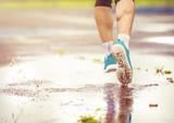 Fototapeta Young man running in rainy weather