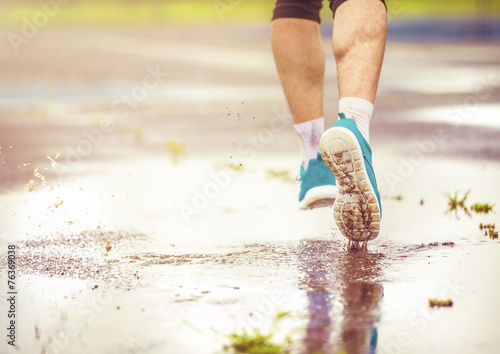 canvas print picture Young man running in rainy weather