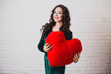 Beautiful happy woman with red heart in hands on Valentine's day