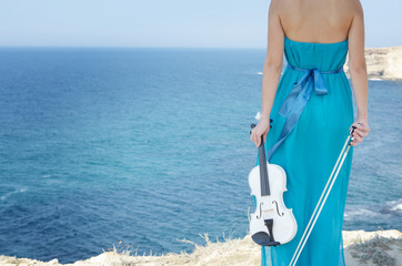 Woman in cyan dress holds violin and bow in her hands