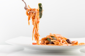 Spaghetti with tomato sauce and courgette on a fork