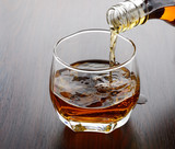 pouring whisky into glass - 76371849
