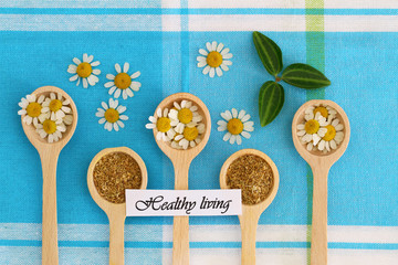 Healthy living card with chamomile flowers on wooden spoons