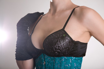 Beautiful young woman in black bra and blue corset